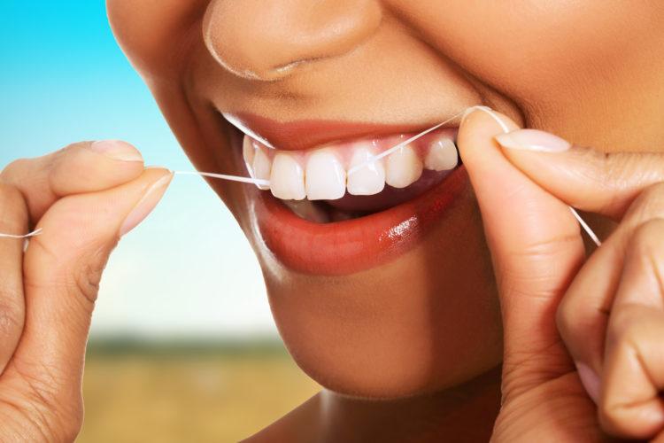 Beautiful woman using dental floss.